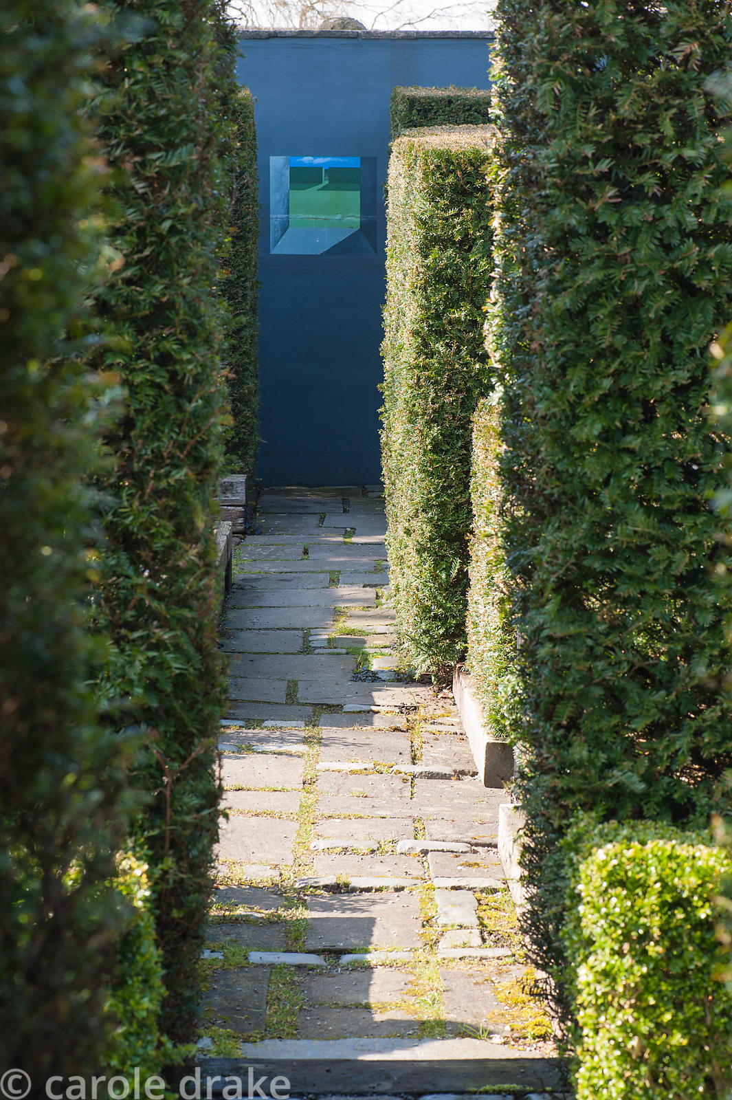 Yew hedges frame a view to a small painted image on a dark grey wall in a formal garden.