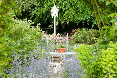 Path lined with catmint, Nepeta 'Six Hills Giant' leads toward white dovecot and bed of irises. Old Rectory, Kingston, Isle o...