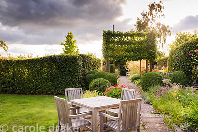 Seating area on the terrace surrounded by clipped box, pleached limes and bright ivy leaved pelargoniums in containers at Far...