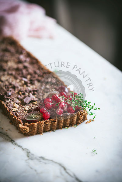 Chocolate tart with biscuit base on a white table.