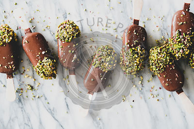 Chocolate glazed ice cream pops with pistachio over marble background