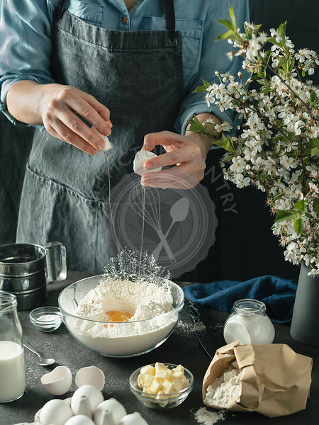Female hands break the egg making bundt cake