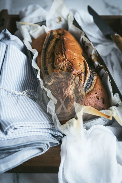 Banana bread loaf amongst linen cloths