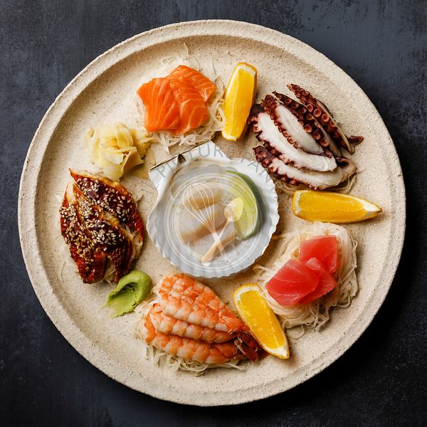 Sashimi sushi set with scallop on shell with daikon and lemon on plate on dark background