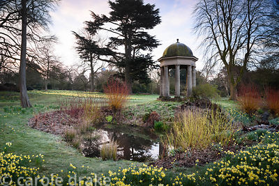 Temple of the Four Winds at Doddington Hall, Lincolnshire on a March morning set beside a small pond fringed with the colourf...