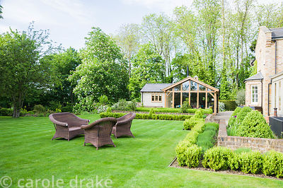 Rattan furniture on the main lawn edged with clipped box.