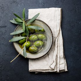 Olives, olive oil and olive branch on black dark background