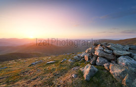 A bright sunset over the mountains of the Lake District from Ramspgill Head with views of the summits of The Knott, Rest Dodd...