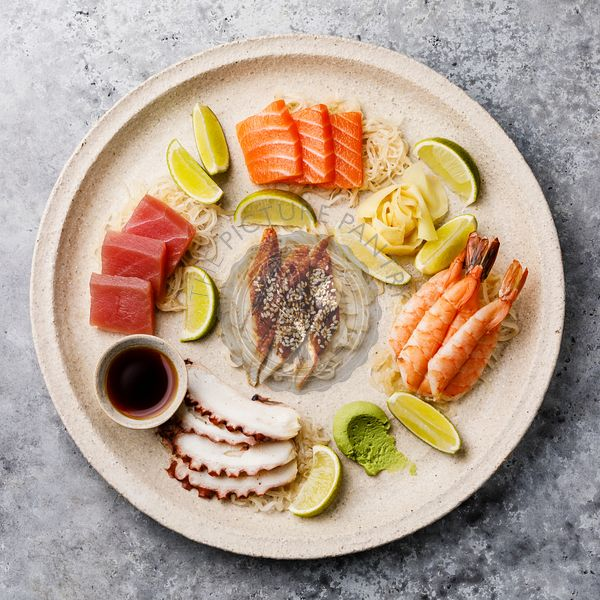 Sashimi sushi set on plate with soy sauce on gray background