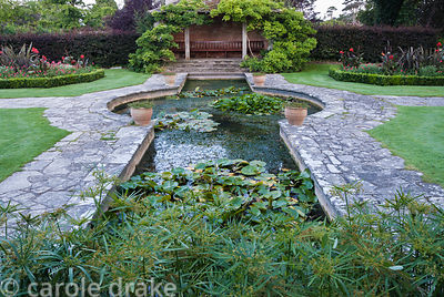 Red Garden has a formal lily pond at its centre with Cyperus alternifolius at its end, and box edged beds planted with scarle...