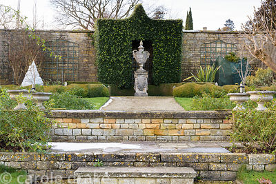An ornamental urn is framed by Quercus ilex in the White Garden at Bourton House in January