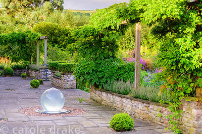 Water sculpture by Allison Armour framed by wisteria on the terrace at the Yeo Valley Organic Garden, Blagdon, Somerset