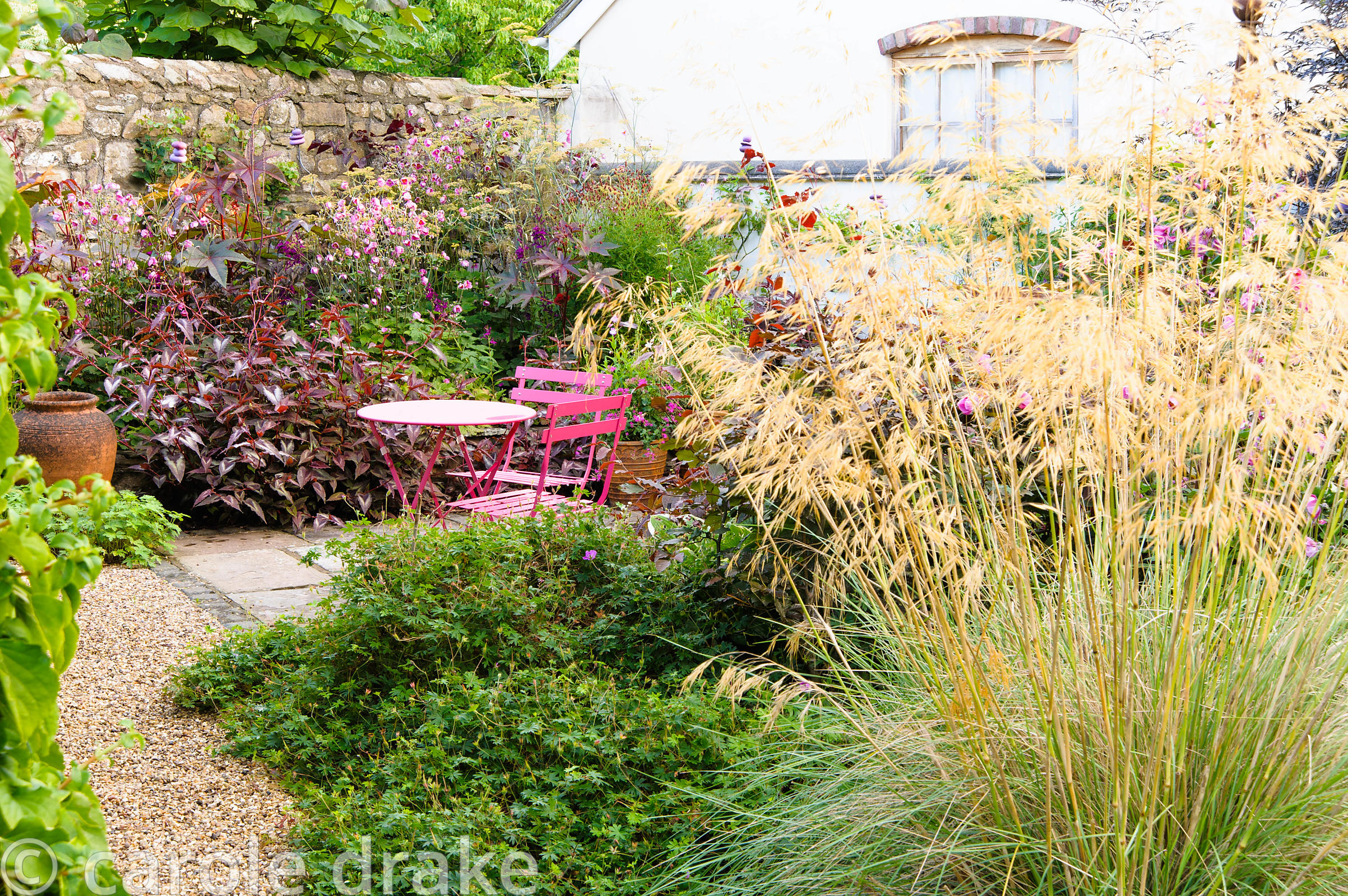 Stipa gigantea marks the entrance to a small courtyard garden planted with purple plants including Persicaria microcephala 'R...
