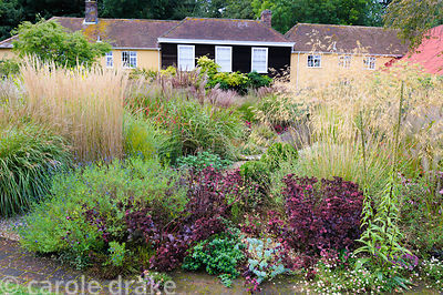 Circular bed planted with a variety of herbaceous perennials and grasses including miscanthus, Calamagrostis x acutiflora 'Ka...