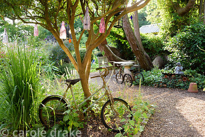 Vintage children's bike and tricycle used as decorative features in Five Oaks Cottage garden in July