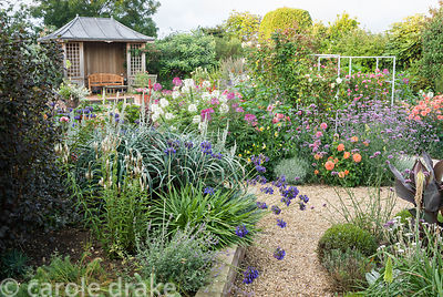 Central pond and summerhouse feature in the sunken garden, constructed in 2005, surrounded by a colourful mass of perennials ...