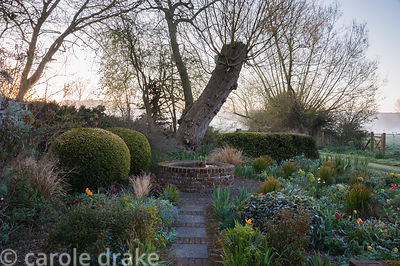 Pollarded willows loom over the front garden featuring a raised brick built circular pond and planting including peonies, eup...