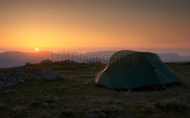 A tent pitched, camping on the mountain summit of Rampsgill Head with views of the surrounding mountains in the Lake District...
