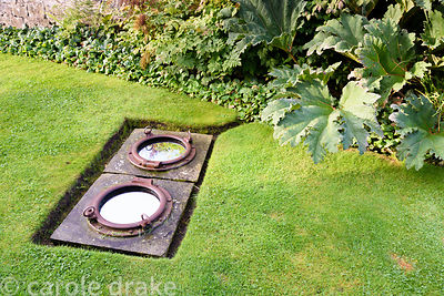 Ship's portholes inset with mirror and set into the lawn at Broadwoodside, Gifford, East Lothian
