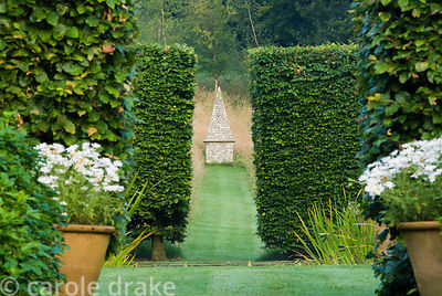 Steps decorated with pots of white daisies lead up to another part of the garden. Through two sets of beech hedges a simple o...