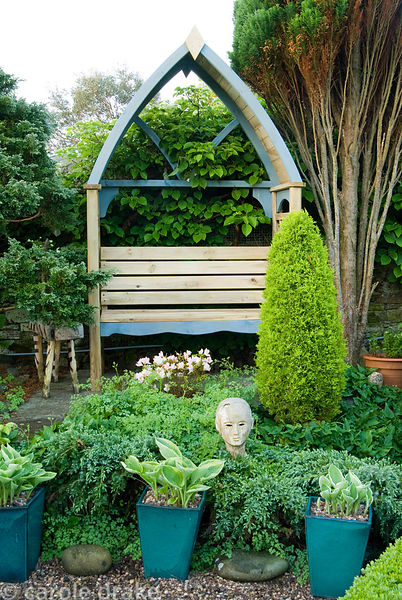 Framed wooden seat is surrounded by evergreens including juniper and pine, with variegated hostas in glazed pots in the foreg...