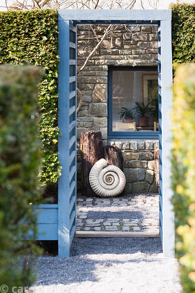 A painted wooden entrance set into yew hedges frames an ammonite and logs below a window in a formal garden.