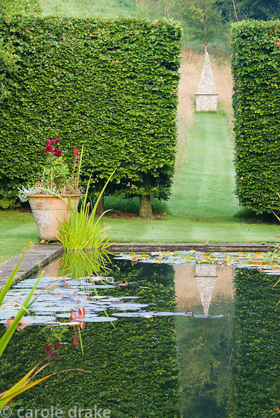 Formal pond in the upper garden where a gap between beech hedges frames an obelisk set in a grassy meadow. Corscombe House, C...