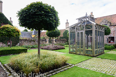 An aviary sits at the centre of the Upper Courtyard surrounded by Acer platanoides 'Globosum' and a chequerboard layout of al...