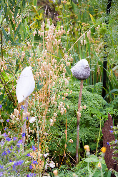 Ceramic birds amongst quaking grass, Briza maxima, at Five Oaks Cottage in July