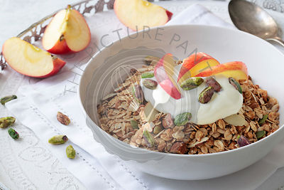 Muesli with yoghurt, slices of apple and pistachio nuts.