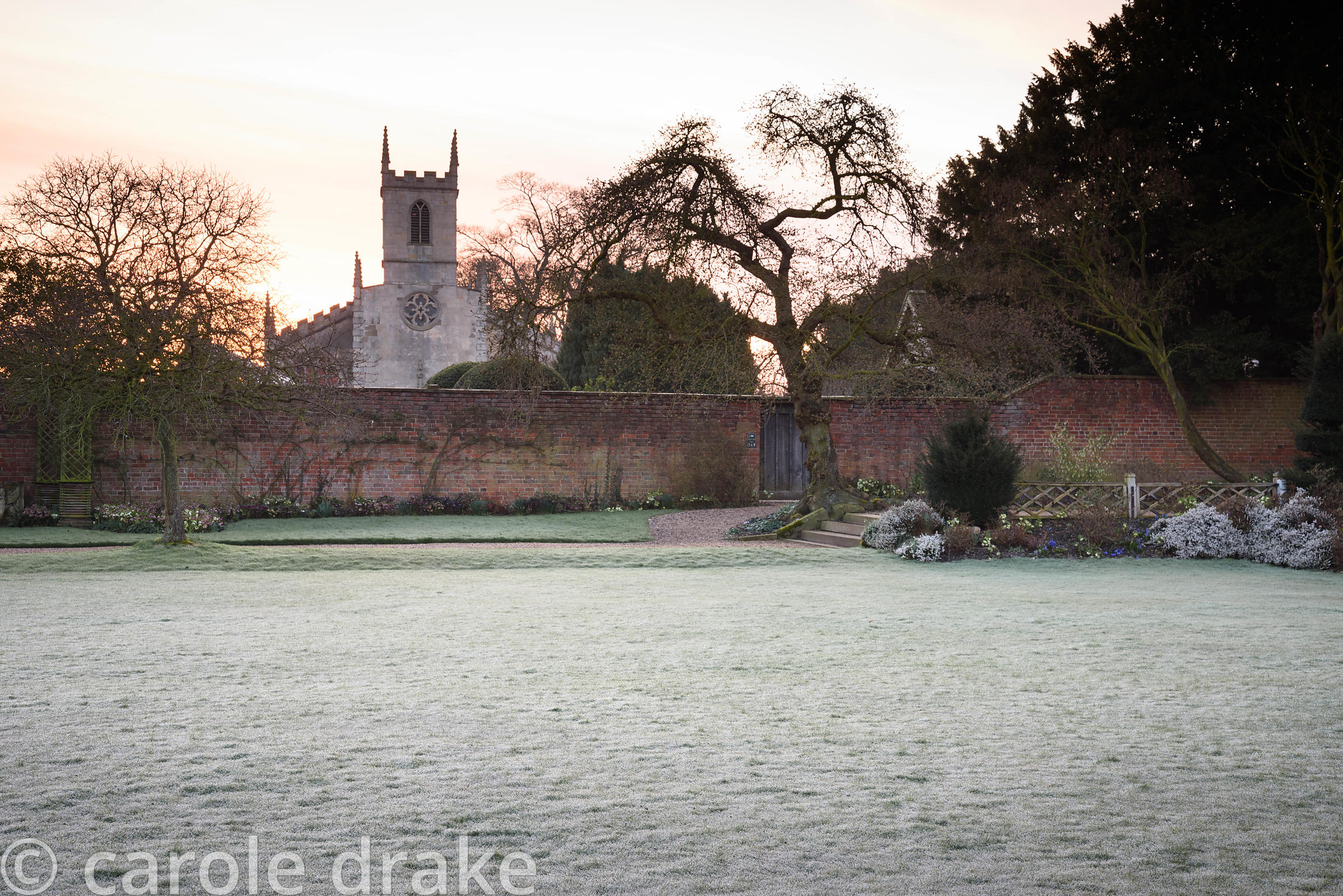 The croquet lawn on a frosty March morning at Doddington Hall, Lincolnshire with St Peter's Church