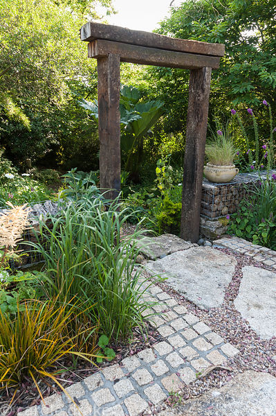 Archway of railway sleepers frames steps from the terrace to the woodland garden, set into a wall made of gabions filled with...