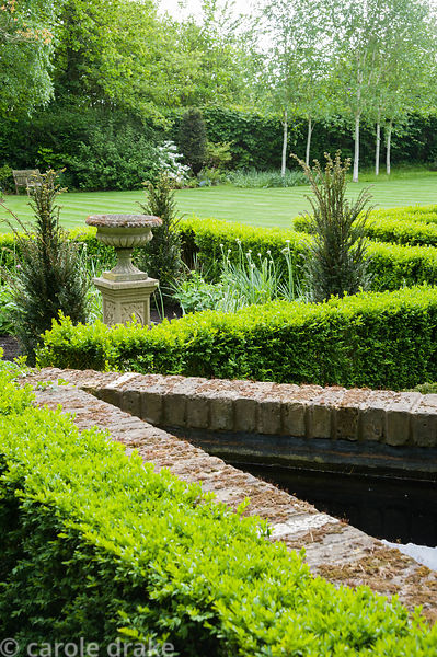 Box edged beds to one side of the house are planted with yews around a central urn.