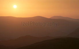 Late evening glow of sunset over the mountains of the Lake District UK from the summit of Rampsgill Head with The Knott just ...