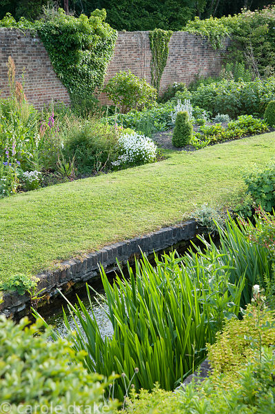 The River Bride runs through the lower part of the walled garden, with a grassy path beside it and vegetable and salad beds b...