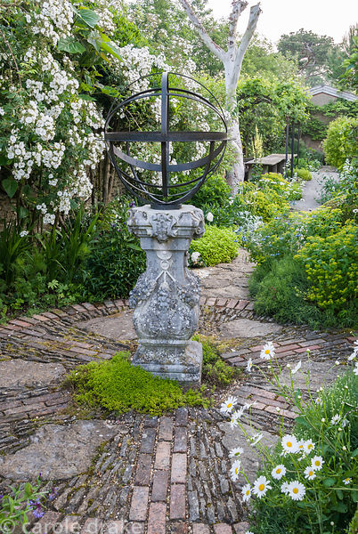 Decorative sundial on brick path framed by white Rosa 'Rambling Rector'. Private garden, Dorset, UK