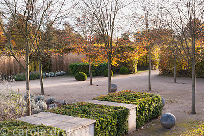 Walled garden designed by Brita von Schoenaich featuring Amelanchier × grandiflora 'Robin Hill', clipped box blocks, stone sp...