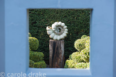 Ammonite sculpture by Darren Yeadon seen through an opening in a painted wall in a formal garden.