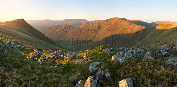 The warm morning glow of sunrise over the summit of High Street with Harter Fell in the distance, Kidsty Pike to the left fro...