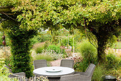 Early autumn in a garden in rural Nottinghamshire where an arbour covered with rambling roses provides a shady dining area on...