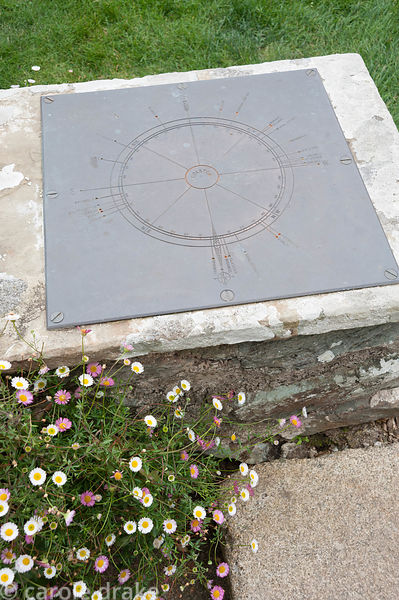 Compass on metal plate with points to far away places marked. Coleton Fishacre, Kingswear, Devon, UK