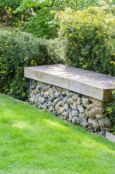 Bench made from a rock filled gabion topped with wood.
