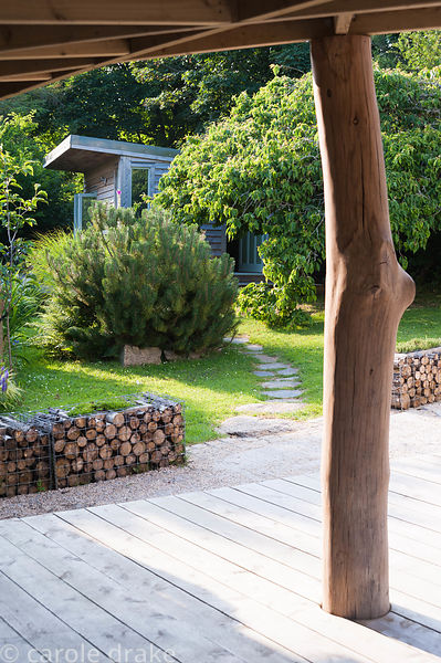 A smoothed tree trunk supports a roof over decking, with log filled gabions and Sara's garden office beyond. The 'Garten' Gar...