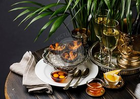 Fresh opened Sea Urchins on ice in silver bowl with quail egg and soy sauce and Champagne on black wooden table