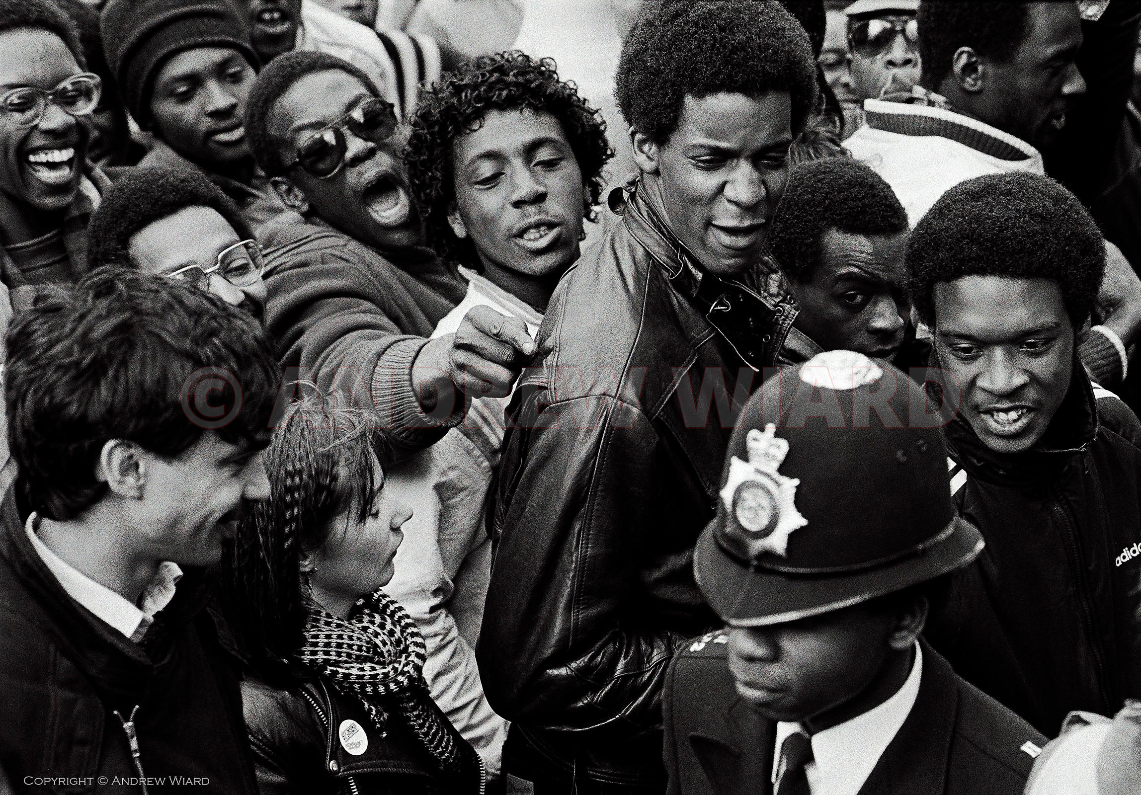 Youths show contempt for a black police officer during a National Demonstration Against Racism in Newham in 1985. The demonst...