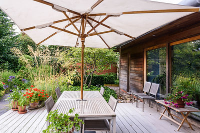 Decking terrace adjoining the kitchen with dining table and chairs under an umbrella, and pots planted with agapanthus and pe...