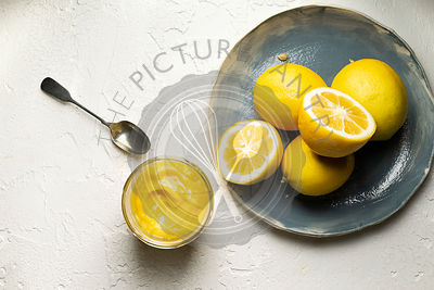 Fresh lemons, whole and sliced in half, arranged on a blue hand made plate. A jar of home made lemon curd and a spoon are alo...