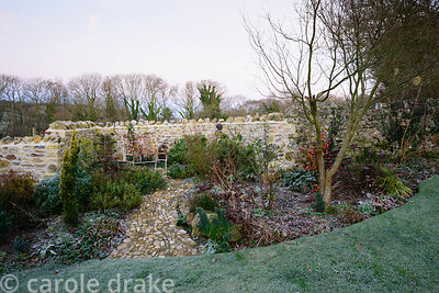 Border beside frosted lawn planted with euphorbias, fastigiate yew, sedums and Physalis alkekengi framing a recently laid sto...