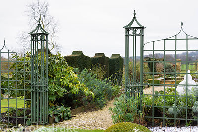 Green painted trellis work frames the entrance to the White Garden containing bold panels of yew at Bourton House in the Cots...