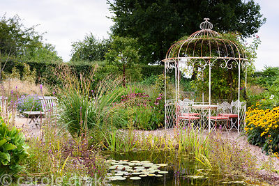 Gravel garden with naturalistic pond, metal gazebo and late season perennials and grasses in rural Nottinghamshire in Septemb...